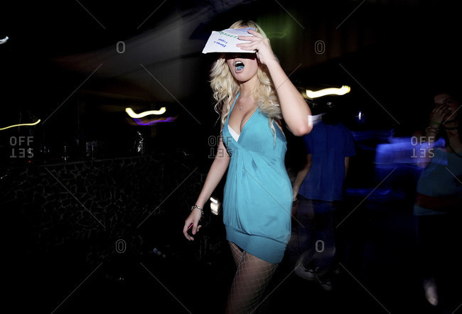 Milan, Italy - July 3, 2010: Young woman with tongue piercing walking in club in short dress