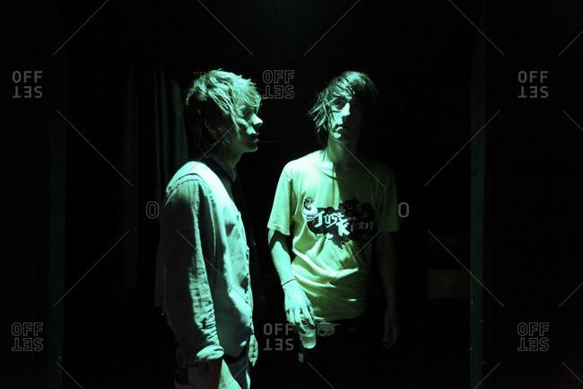 Milan, Italy - July 3, 2010: Two young hip club kids standing in dark of club