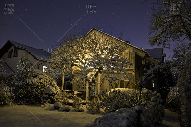 Lighted one-family house with snow-covered garden in the foreground