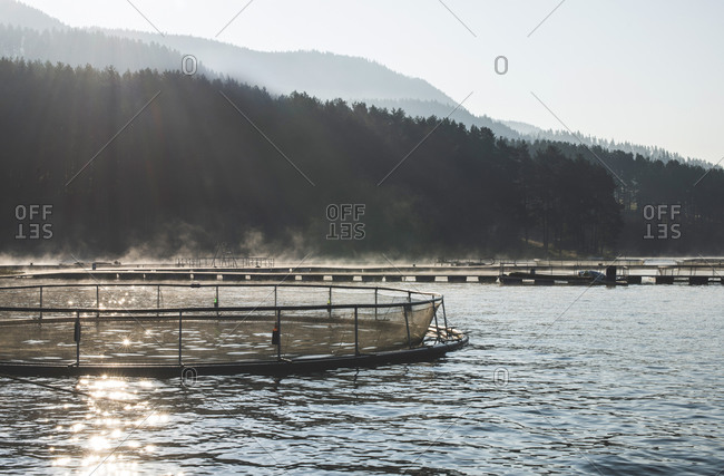 Sun shining on cages for fish farming in mountain lake