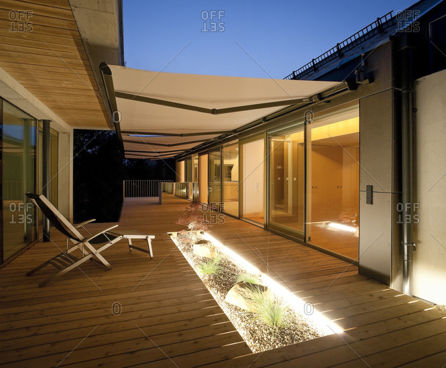 One family house with wooden terrace with awnings in the evening