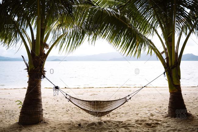 Hammock and palm trees on a beach near El Nido