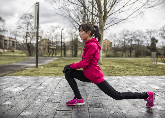 Young woman in a high lunge in park