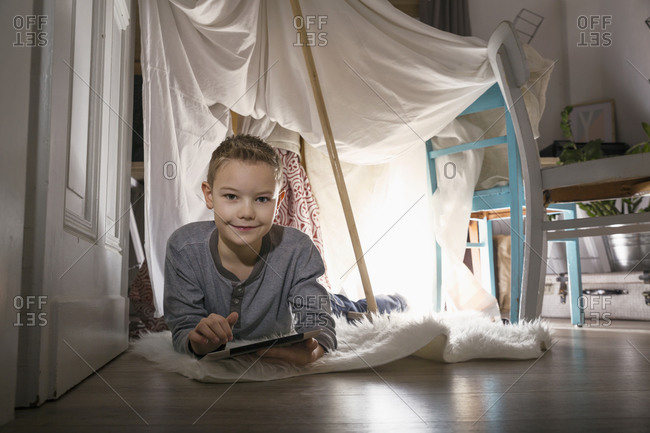 Boy digital tablet lying in self-made tent at home in the evening