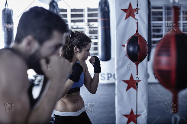 Man and woman exercising with punching bags