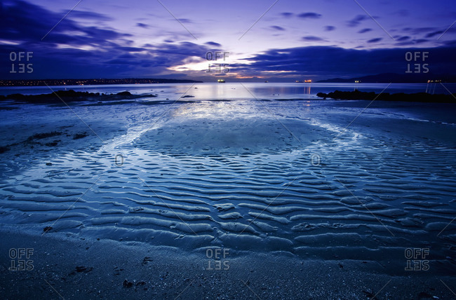 Low angle view of ripple pattern on sand on a beach at low tide under a darkening sky