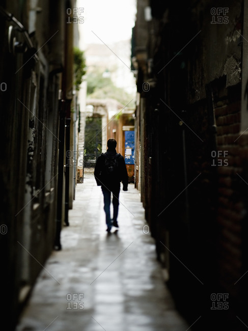 A man walking down a narrow alleyway, Venice