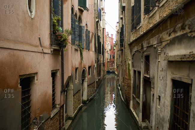 A narrow canal with historic buildings rising from the water, Venice