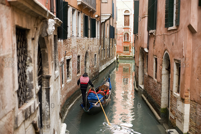 A gondola boat gliding down a small narrow waterway, between historic houses in the city of Venice
