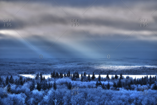 View over the landscape of pine forests, snowfields and shafts of sunlight reflecting on the surface of a lake