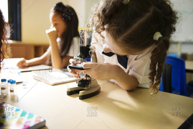 Child using a microscope in science class