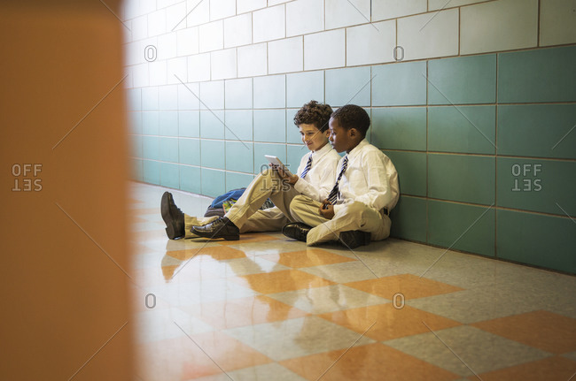 School boys using digital tablet in a hallway of a school