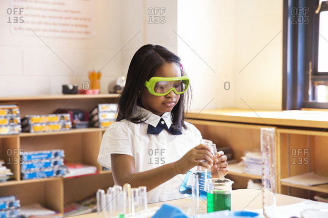 School girl doing a science experiment in class