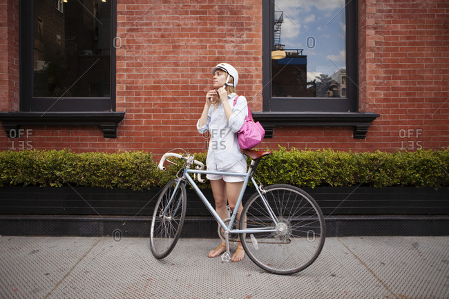 A woman buckles her helmet before a bike ride