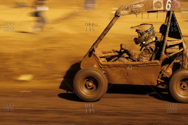A muddy go-kart racking down a track