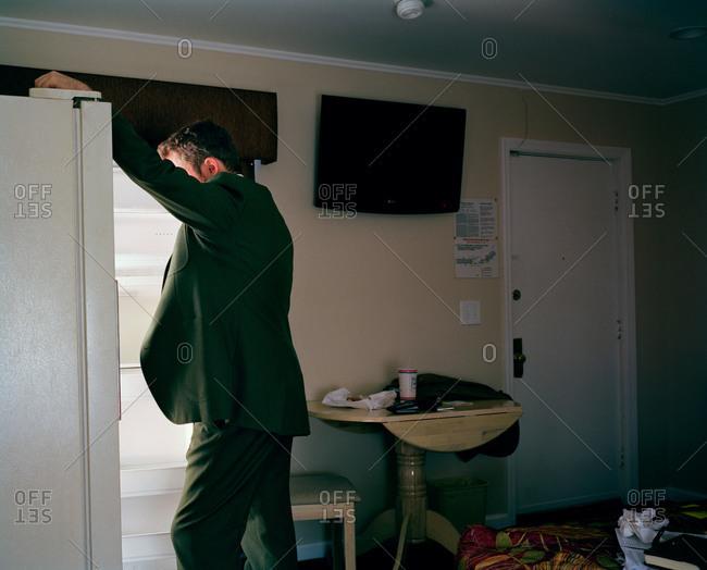 Man opening a fridge in a motel room