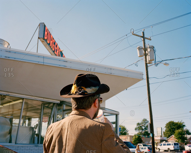 Cowboy sipping a drink at a diner