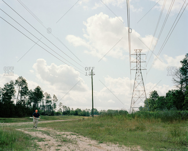 Architect walking nearby power lines