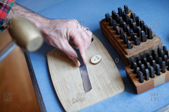 Man engraving letters on a wooden board