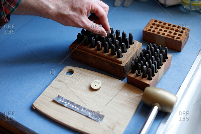 Person engraving letters on a wooden board