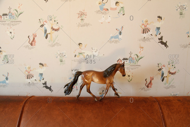 Plastic horse toy in front of wallpaper