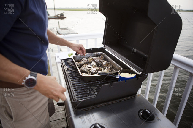 Close up of a man grilling fresh oysters