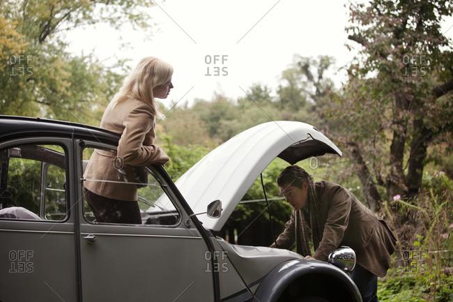 Man fixing a broken down vintage car