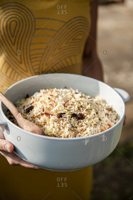 A woman carries a bowl of rice mixed with dried fruit