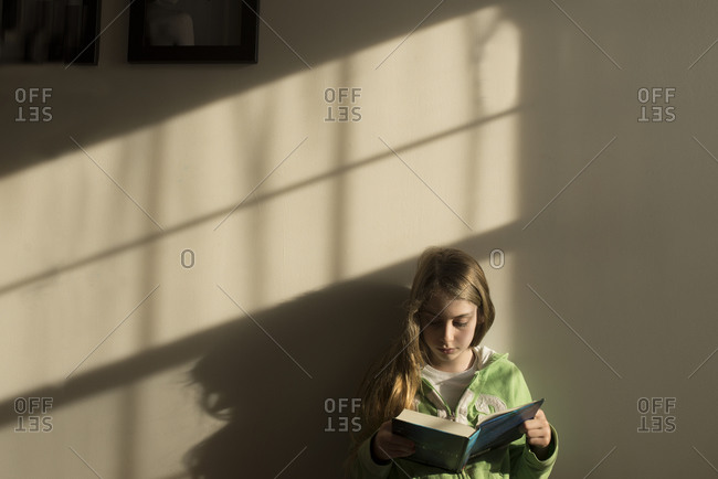 A girl leans against a wall reading a book