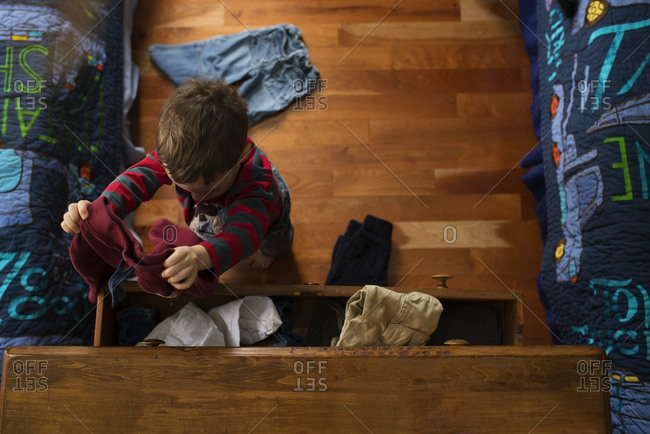 A boy takes clothes out of his dresser