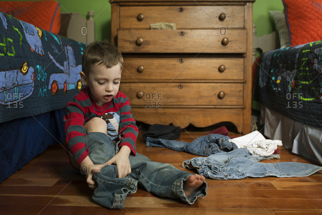 A little boy puts on a pair of jeans