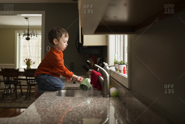 A little boy rinses off a mug