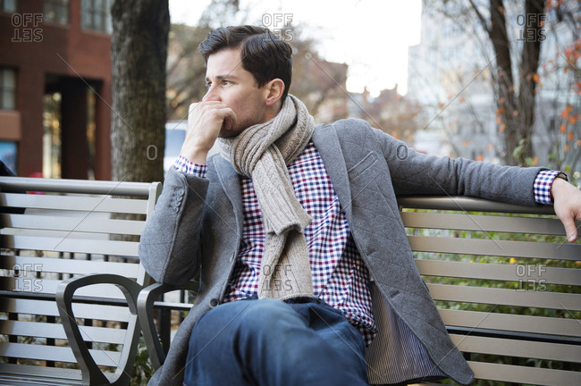 Man waiting on a city park bench