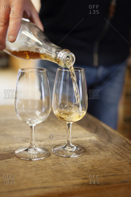 Person pouring wine into wine glasses