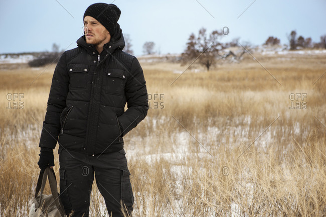 Young man in winter field holding bag