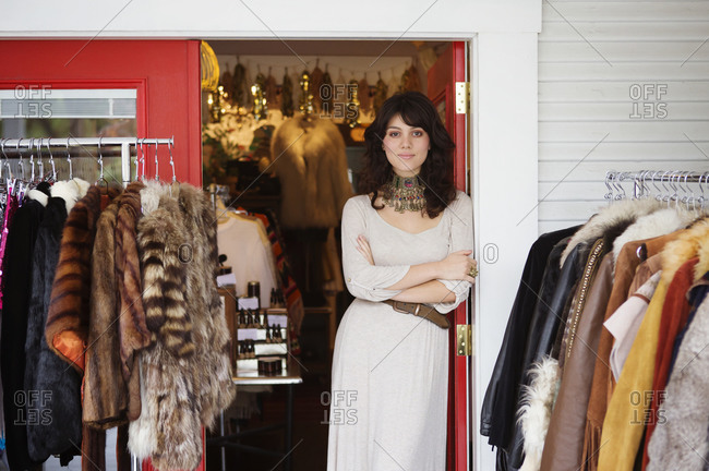 Stylish young woman standing in doorway of her boutique