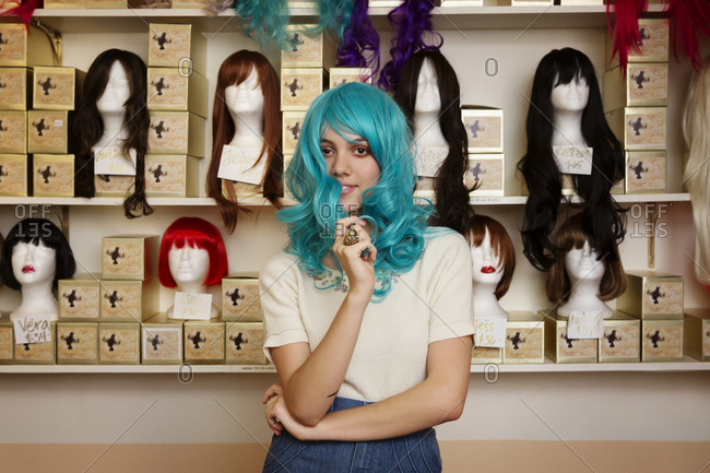 Young woman trying on wig in shop