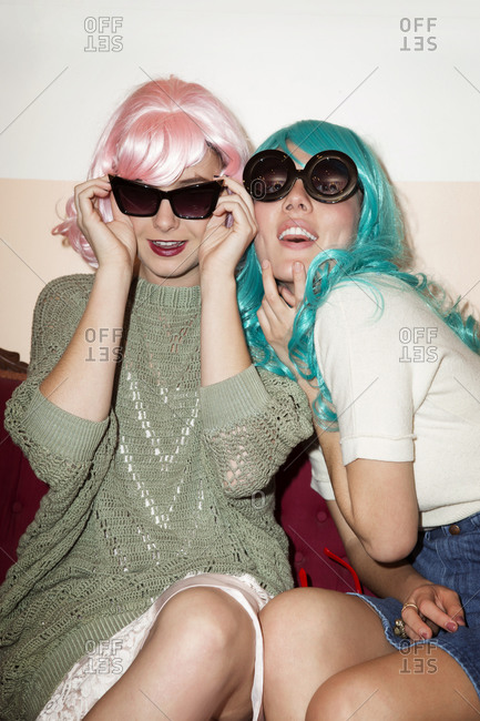 Two young women playfully dressed in wigs