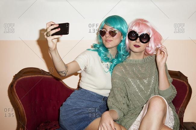 Two young women taking selfies in wigs