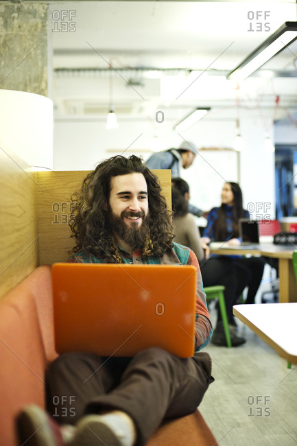 Young man sitting with a laptop