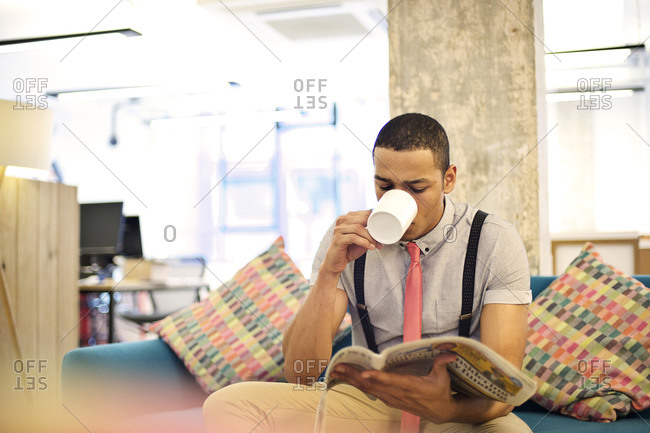Young man having a coffee break in the office