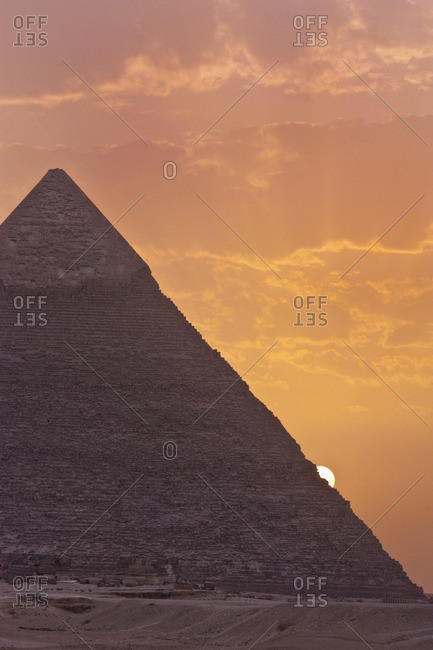 The sun setting behind the Pyramid of Khafre in Giza, Egypt