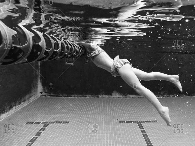 Underwater view of child holding onto swim lane rope