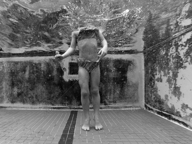 Underwater view of child standing in a swimming pool