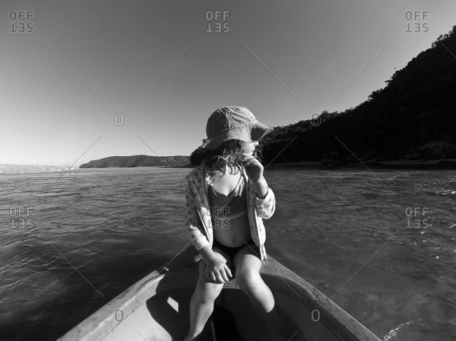 Girl seated on bow of canoe
