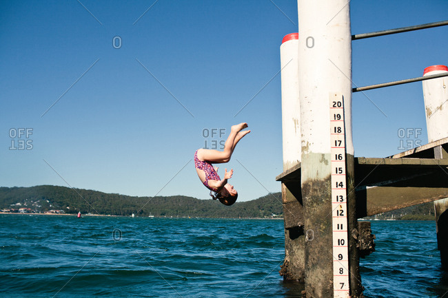 Girl doing a flip off a dock into the water