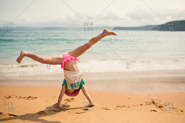 Child doing a cartwheel on the beach