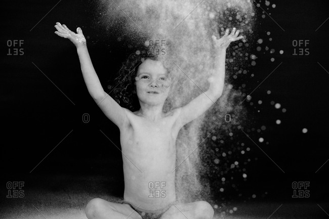 Young child throwing flour in the air