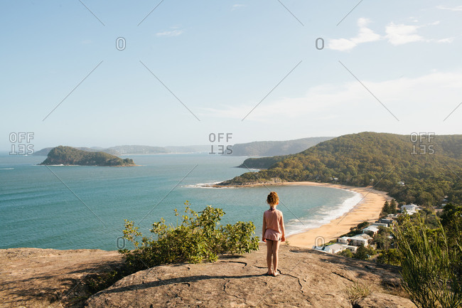 Child standing on rocks overlooking a beach