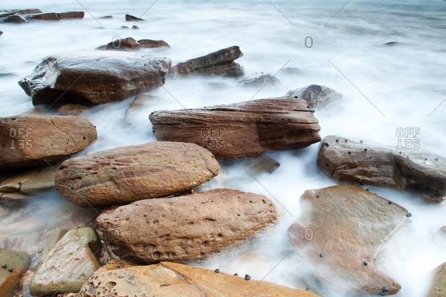 Waves washing over rocks at beach